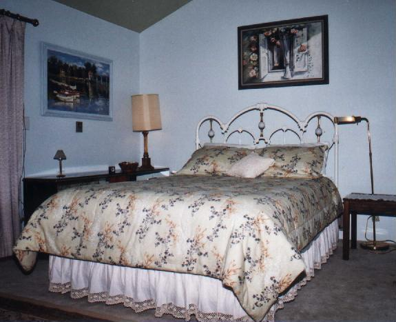 Picture of the master bedroom, includes queen size bed with white iron victorian headboard, a picture on the wall of a boat on the water and a picture of flowers around a shuttered window