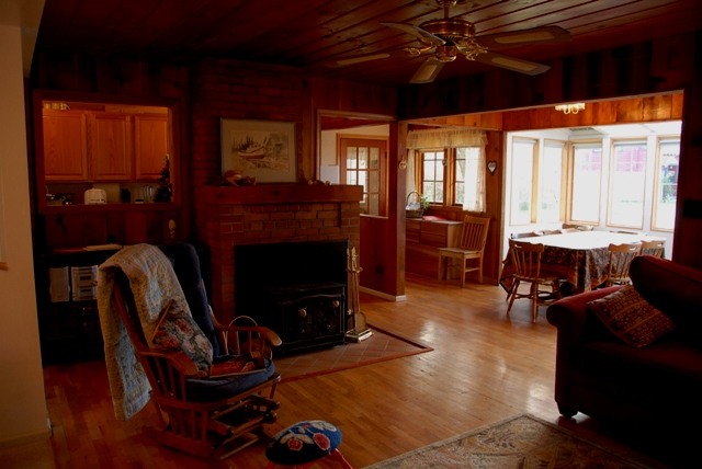 Picture of the living room and fireplace at Seashell Cottage.  Dining area shows in the background to the right