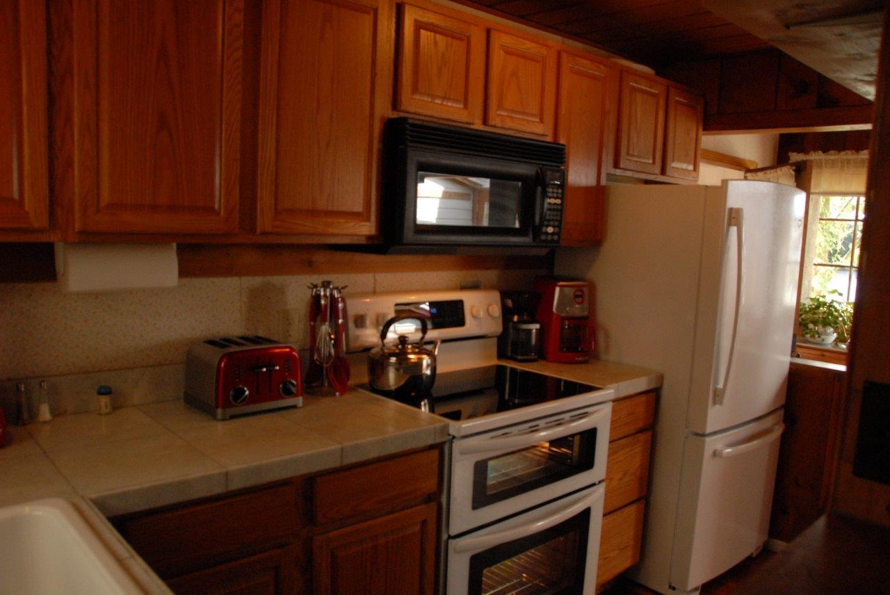 Picture of this is the kitchen at Seashell Cottage.  There is a ceramic top stove, a microwave, dishwasher and Kitchen Aid stand mixer